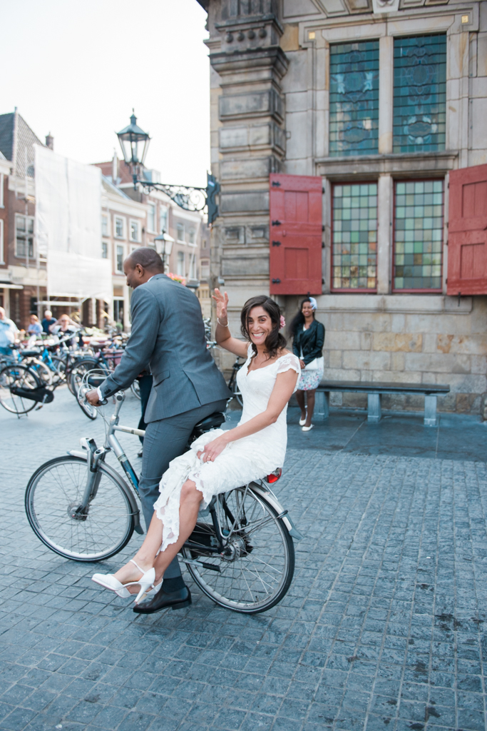 Bride and groom on a bike coming out of the Delft city hall in The Netherlands