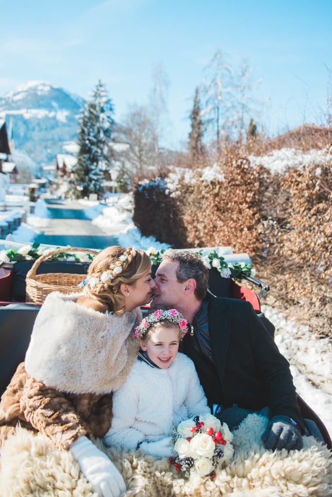 Bride, groom and flower girl in a sleigh in Austria during a winter destination wedding