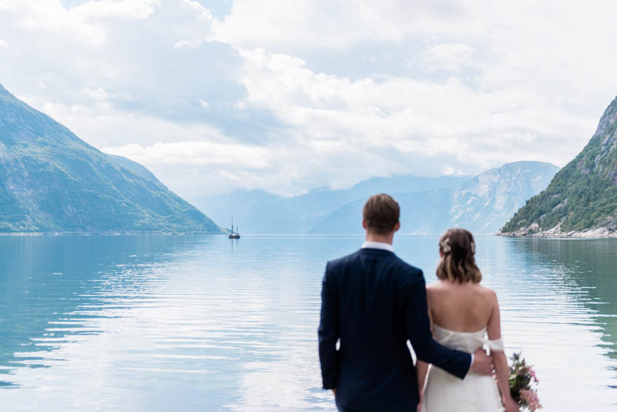 A bride and groom looking into the far distance in a fjord in Norway