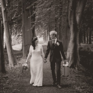 Black and white wedding photo of a bride and groom with a suitcase in a forrest in Schoonhoven in The Netherlands in Europe
