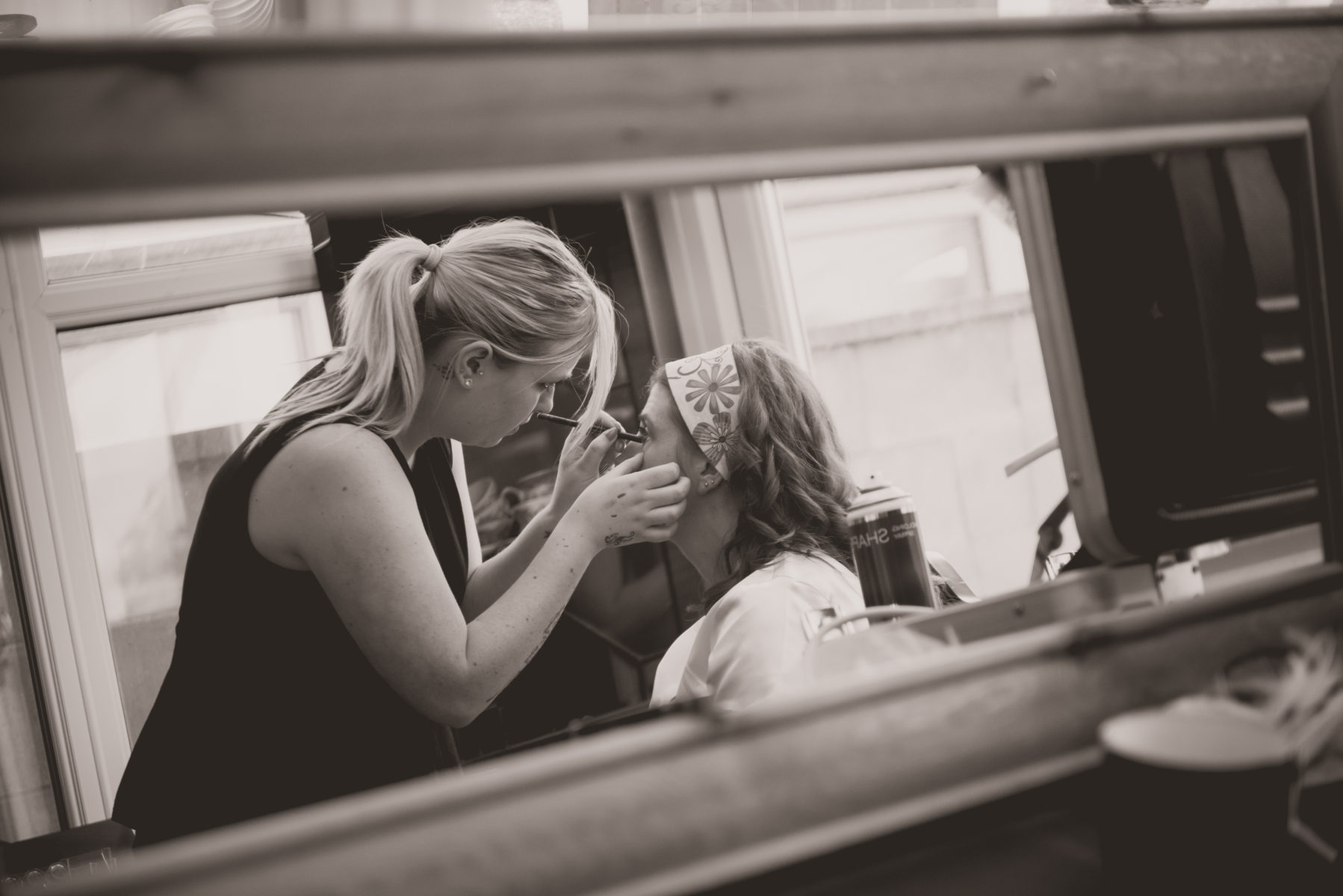 A black and white journalistic wedding photo of a bride getting ready at her home in Corsham
