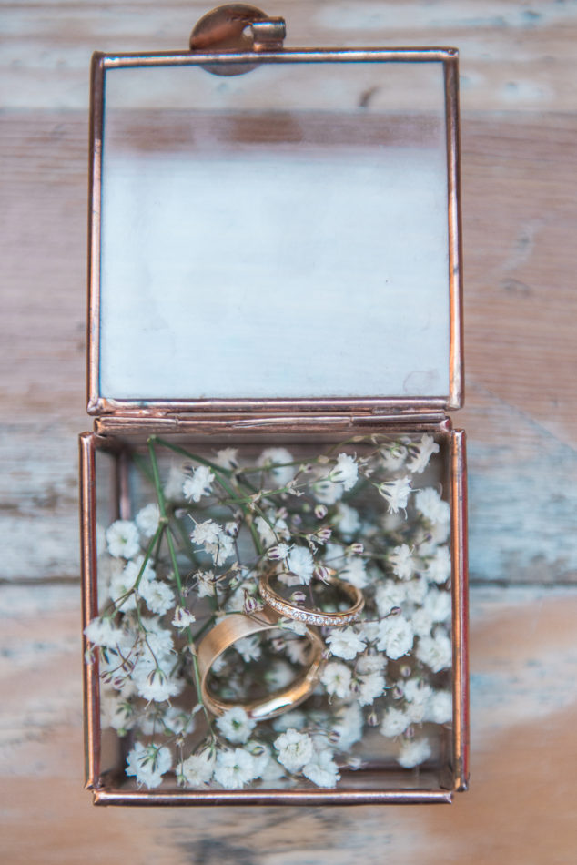 Gold wedding rings in a copper glass ring box
