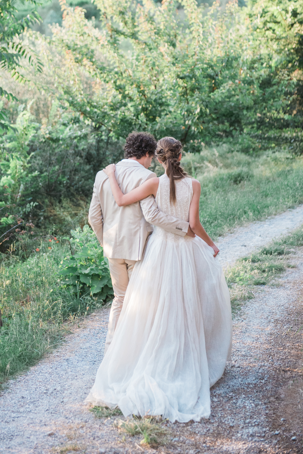 A bride and groom walking on a path in Tuscany, Italy