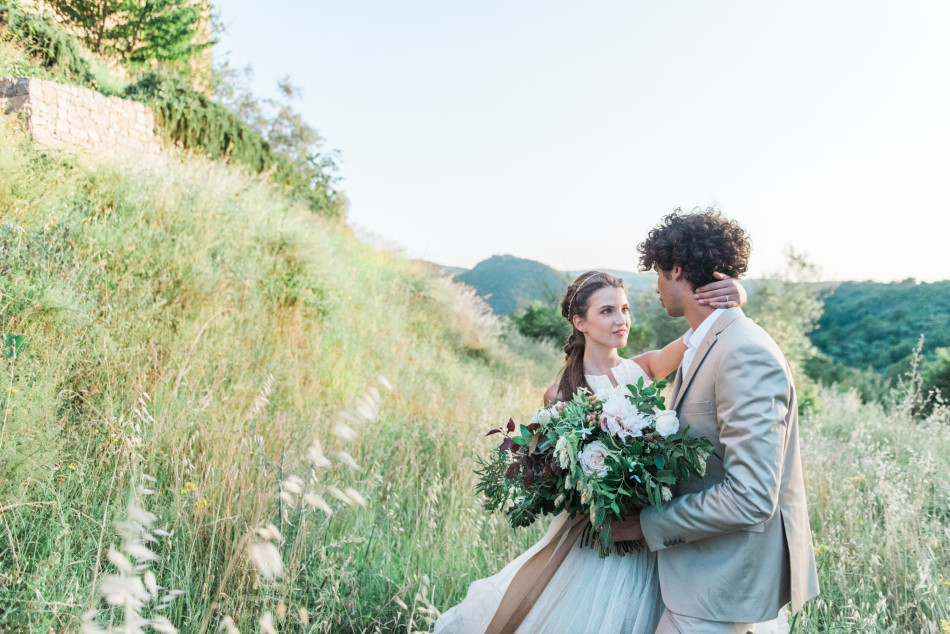 A bride and groom with a flower bouquet at Castello di Potentino in Tuscany in Italy in Europe, shot by wedding photographer Wit Photography