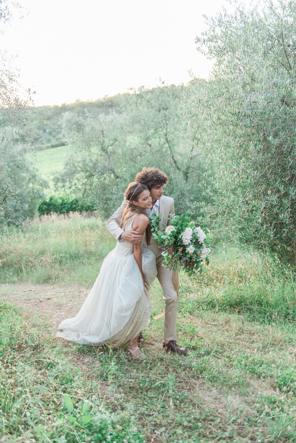 A bride and groom hugging while they walk
