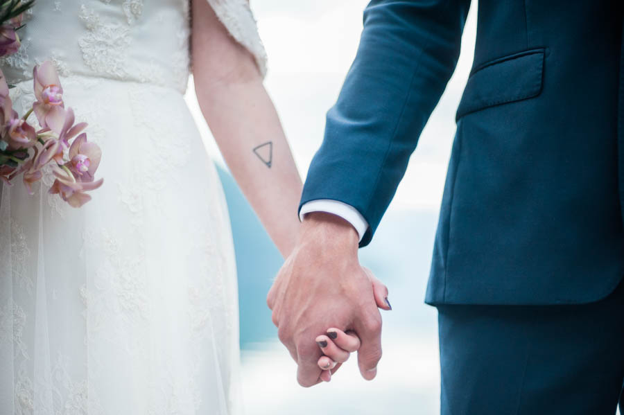 bride, wearing a sibo design dress, and groom holding hands in norway