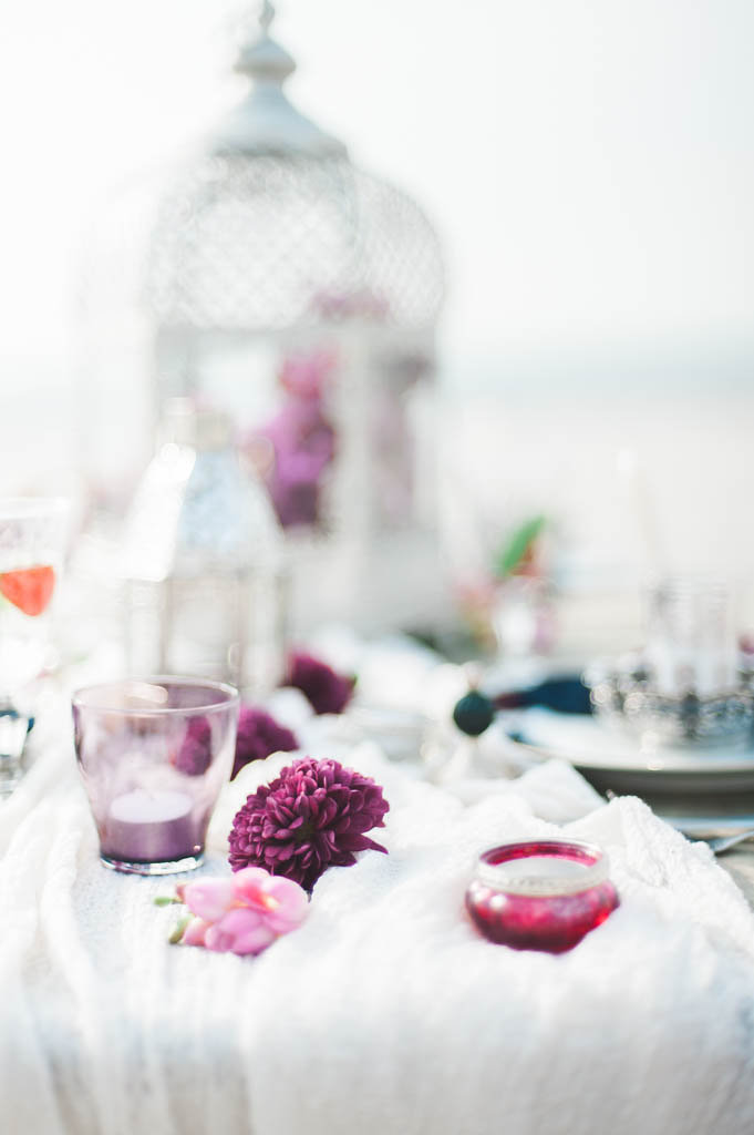 Table with a white table runner and purple accesories