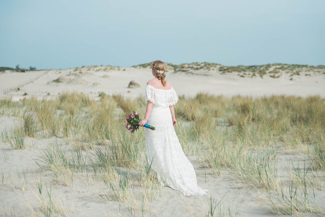 A bride wearing a Daughters of Simone dress in the dunes of The Netherlands