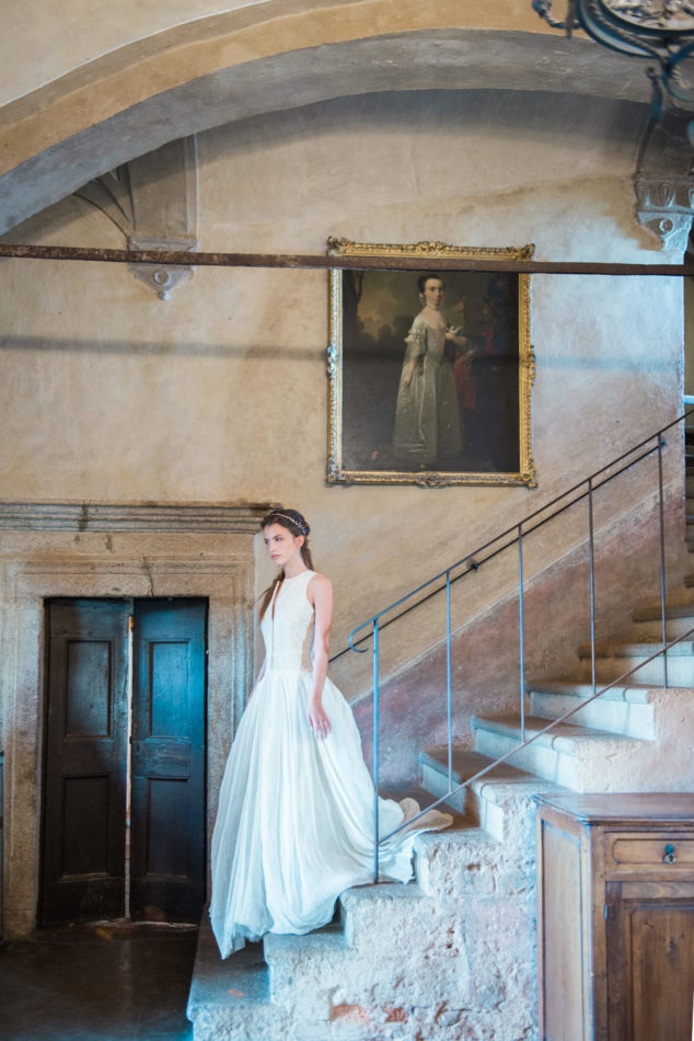 A bride on the stairs of Castello di Potentino, photographed by a destination wedding photographer