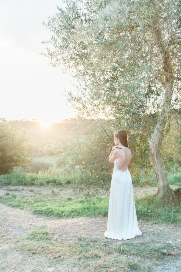 Bride in a modern bohemian wedding dress watching the sunset over the Tuscan hills in Grosseto in Italy, shot by european destination wedding photographer Wit Photography.