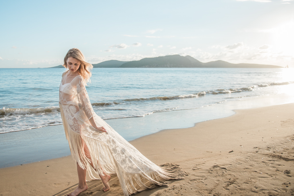 Bride At Her Beach Destination Wedding Walking Near The Sea During Sunset