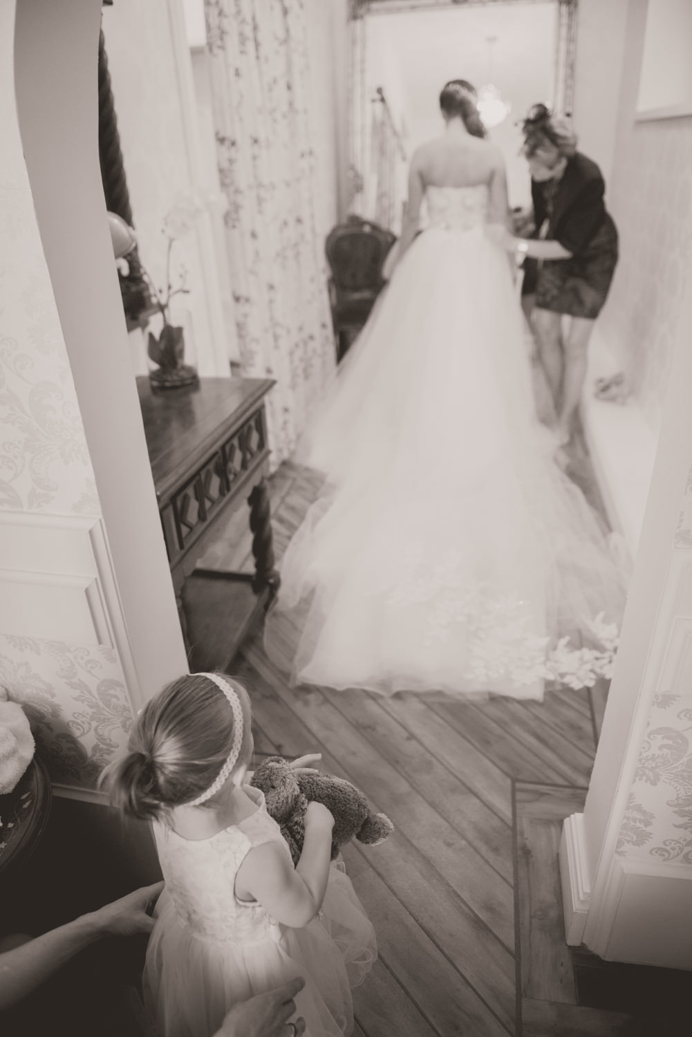 Flower girl looks at the wedding dress in awe at a wedding at Drumtochty Castle