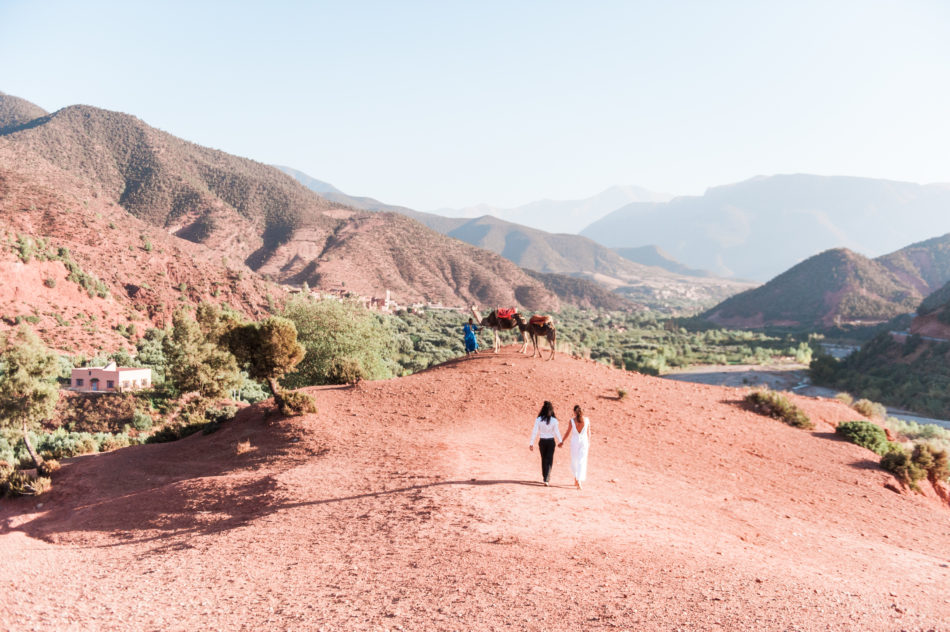 A bride in a jumpsuit and groom with long hair walk in the hills captured by a Wedding photographer in Greece
