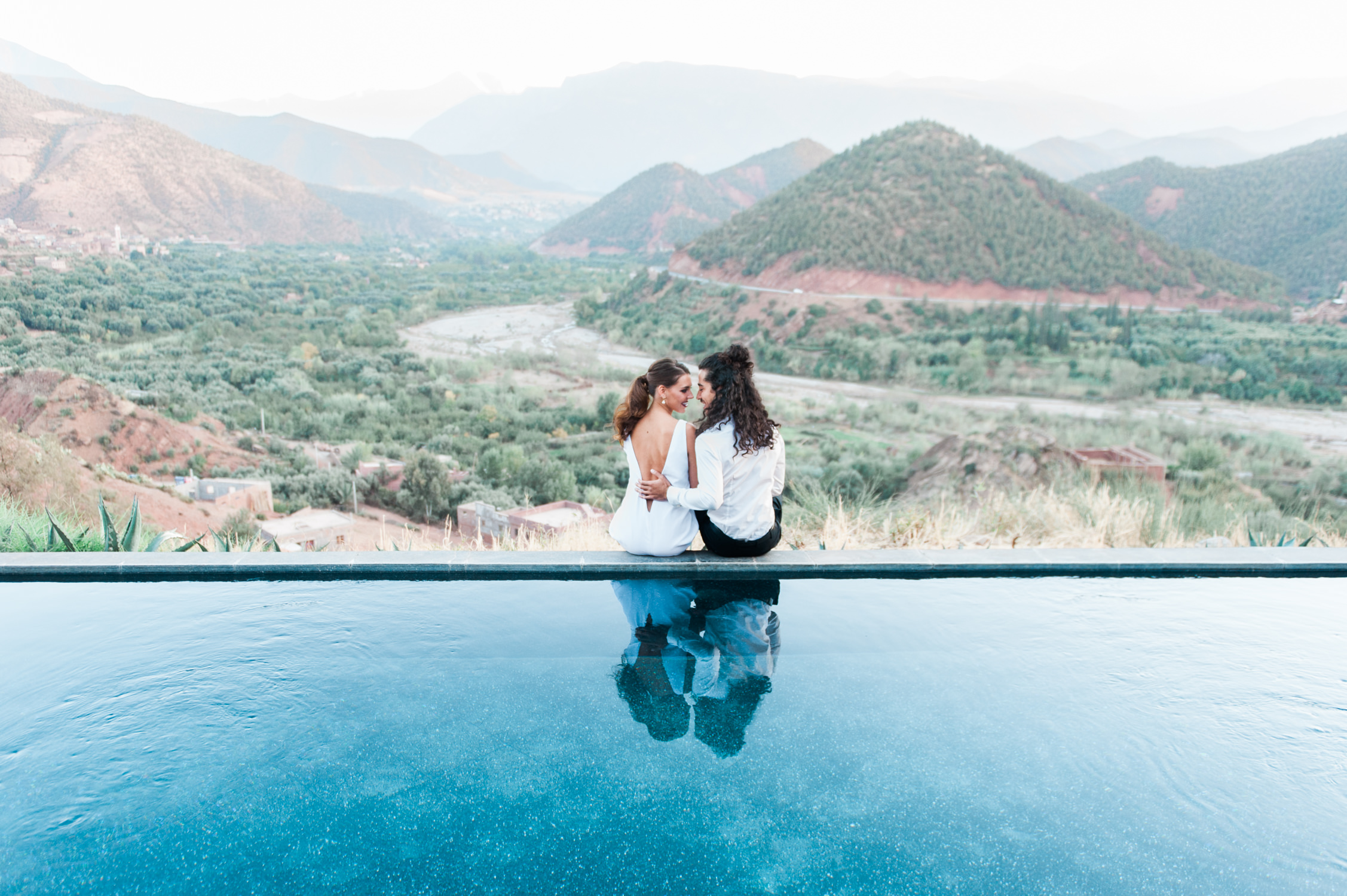 A bride in a jumpsuit and groom with long hair sit at the edge of the infinity pool captured by a Wedding photographer in Italy