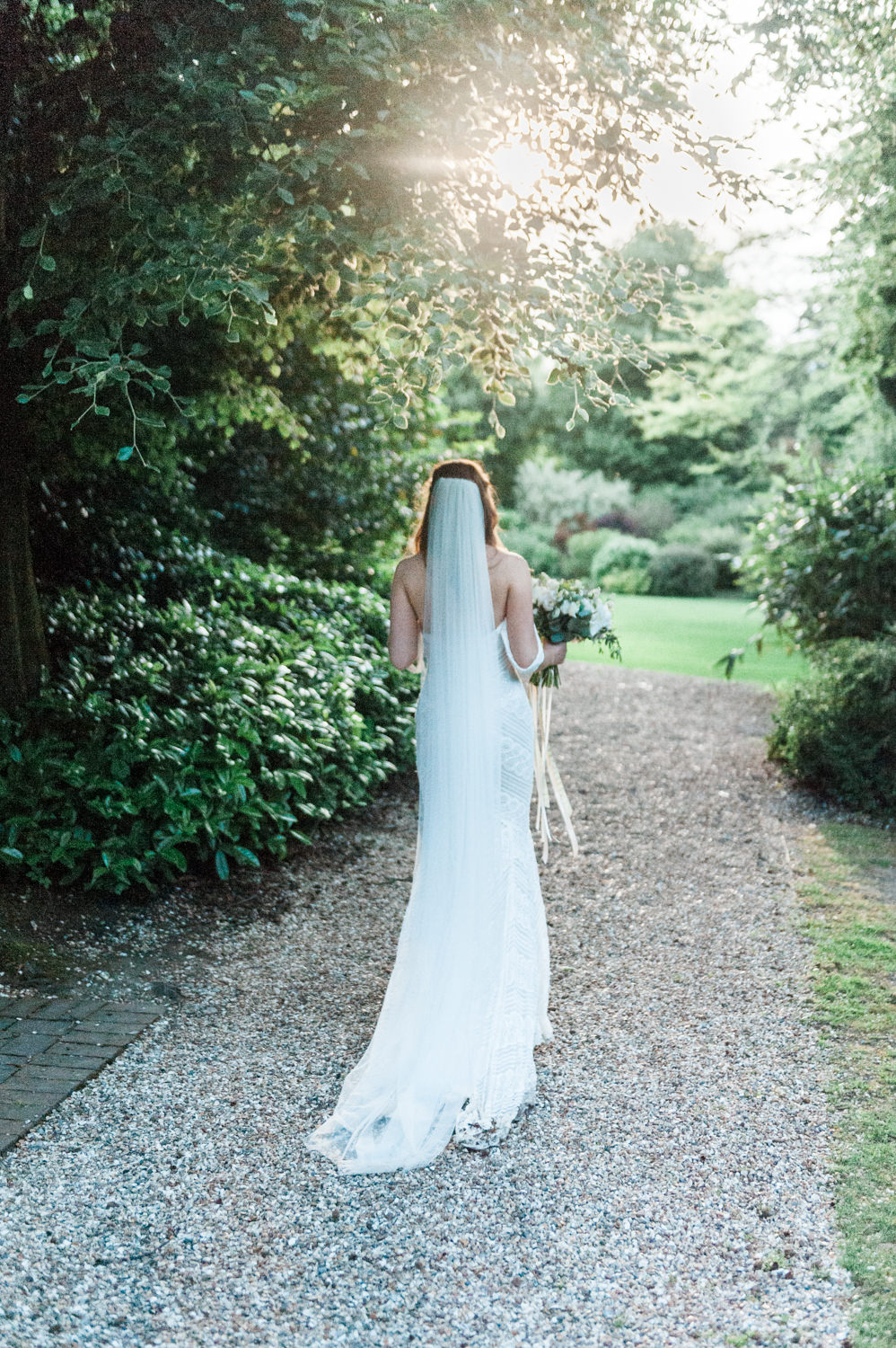 A bride during sunset at her wedding at Larmer Tree Gardens