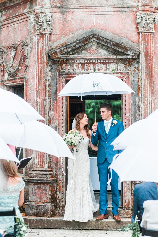 A wedding ceremony in the rain in Larmer Tree Gardens