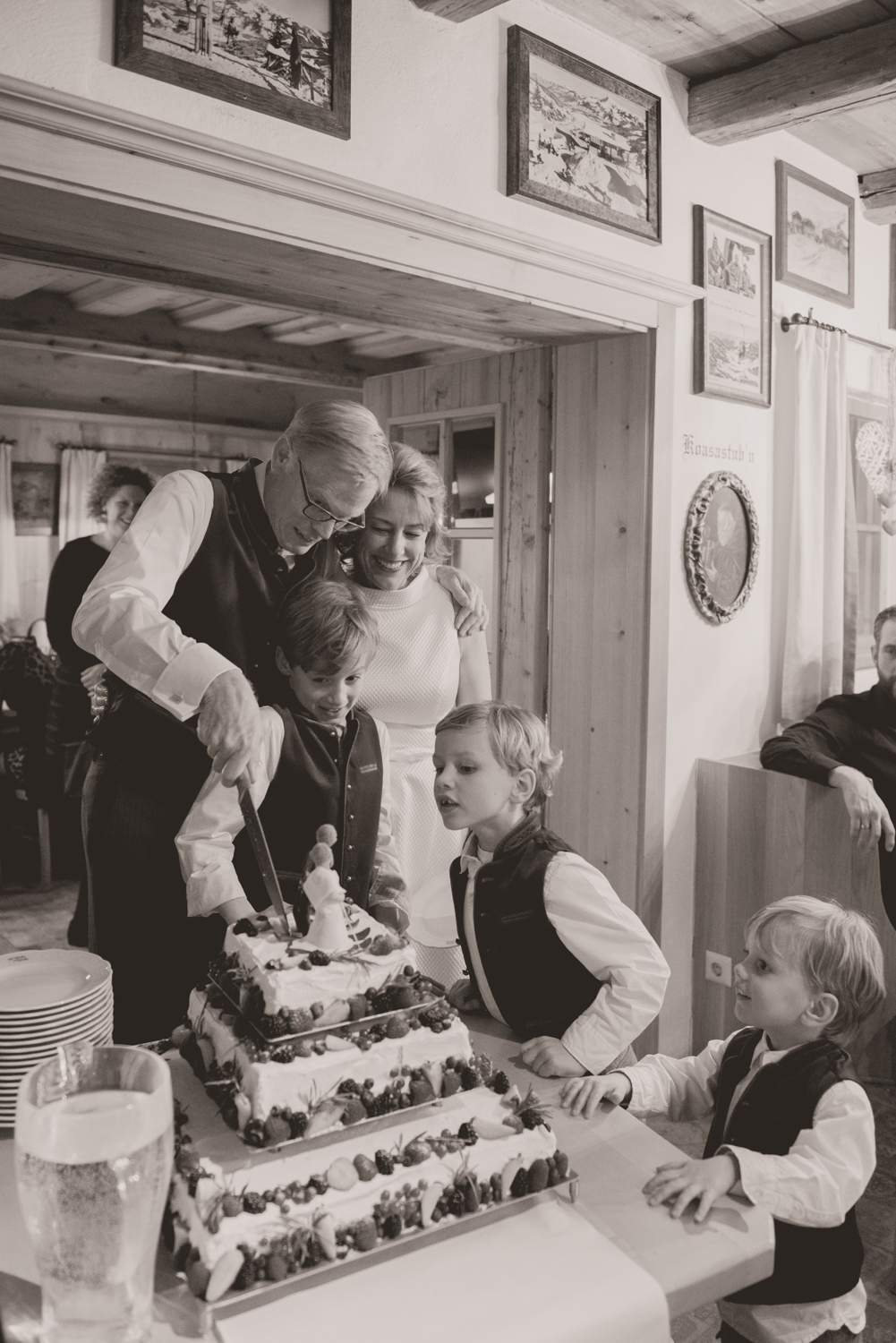 A bride, groom and their children cutting their ski themed wedding cake at their winter wedding in Austria