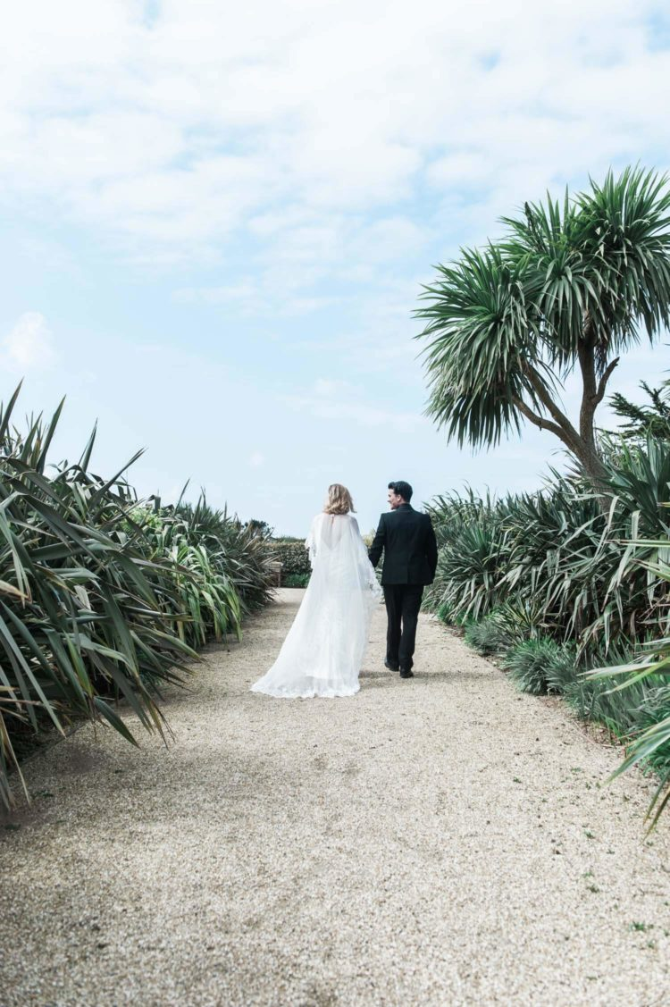 image of a bride and groom walking on a path between tropical plants to illustrate a testimonial of happy customers of Wit destination wedding photography