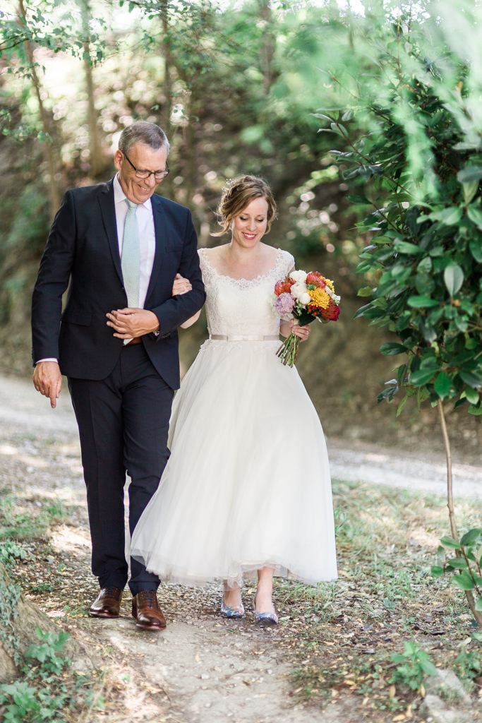 Bride is walked down the aisle at her outdoor wedding at Villa Marsi in Le Marche in Italy