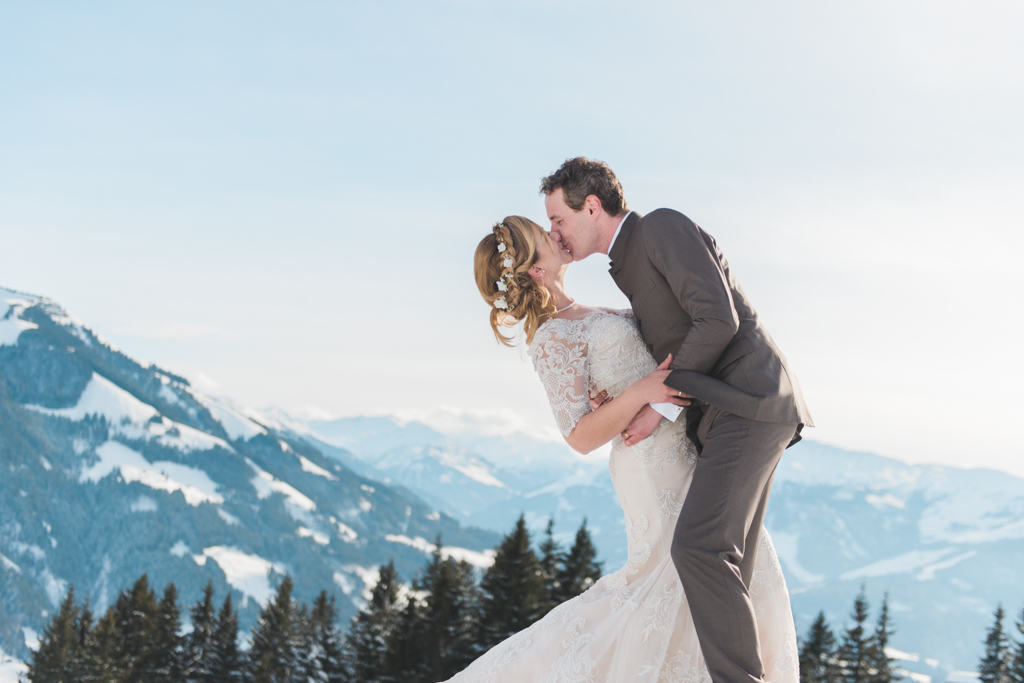 A bride and groom on a snowy mountain in Brixen im Thale in Austria