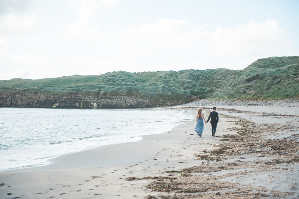 Bride and groom walking on a beach in Ireland during their elopement