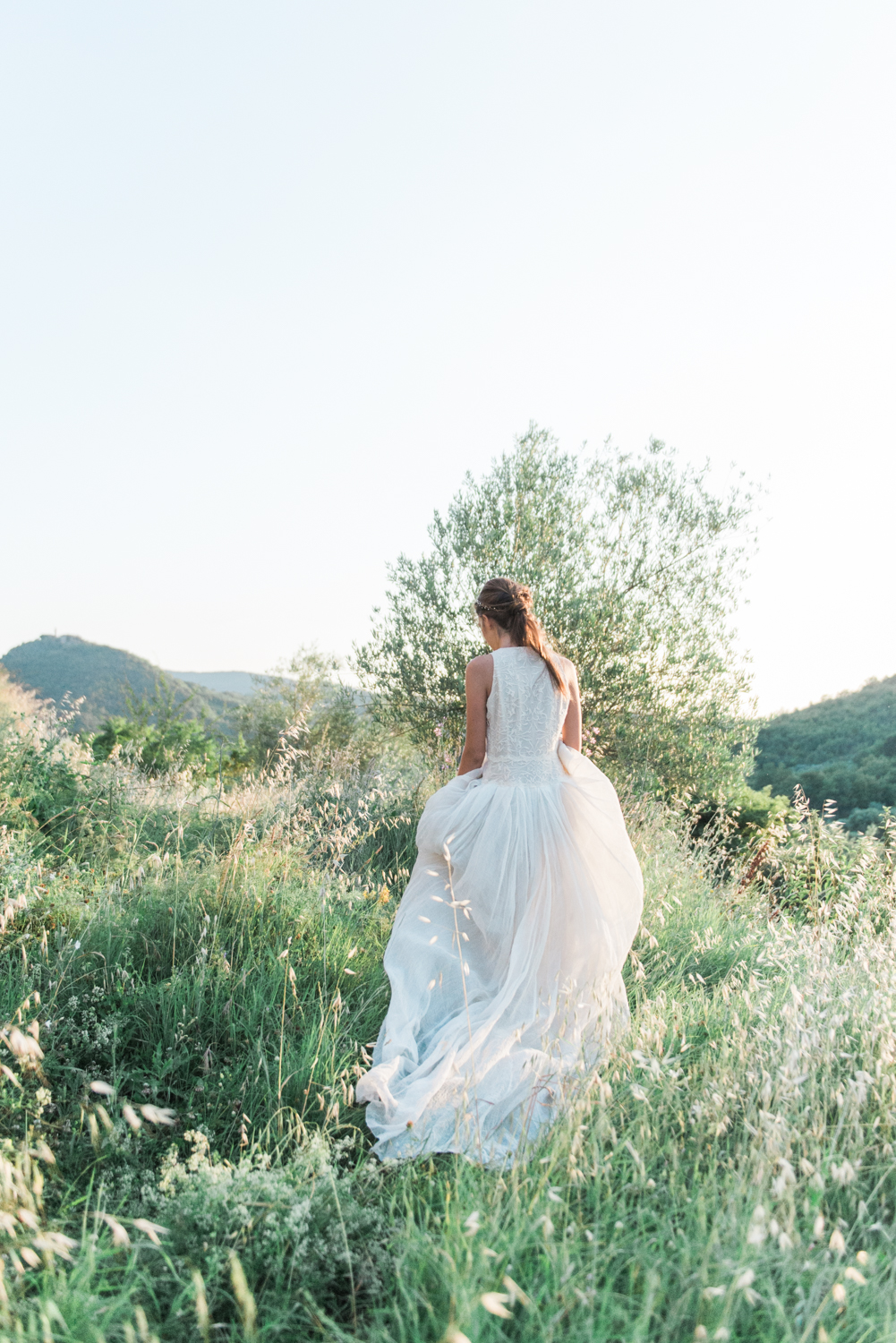 A bride in a Maria Louisa Rabell dress in a field on a hill in Italy