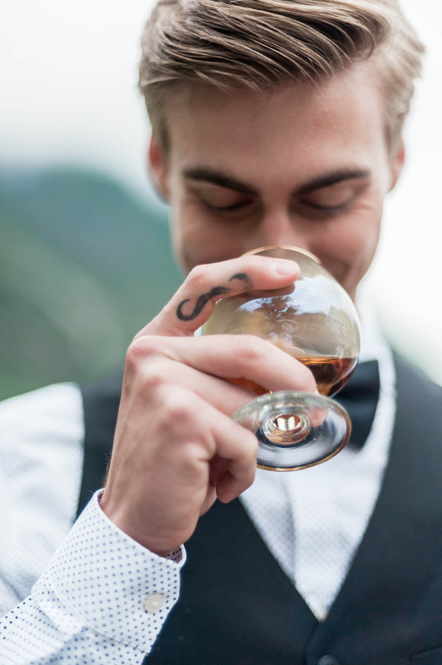mustache tattoo on finger of a laughing groom holding a glass of whiskey in eidfjord in norway