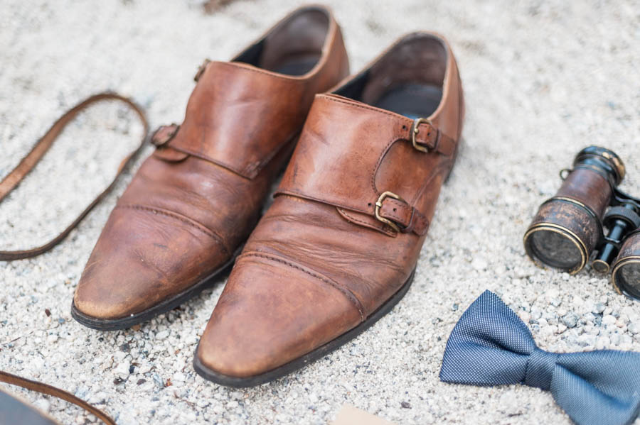 A groom's brown leather shoes with clasps on a beach in Norway