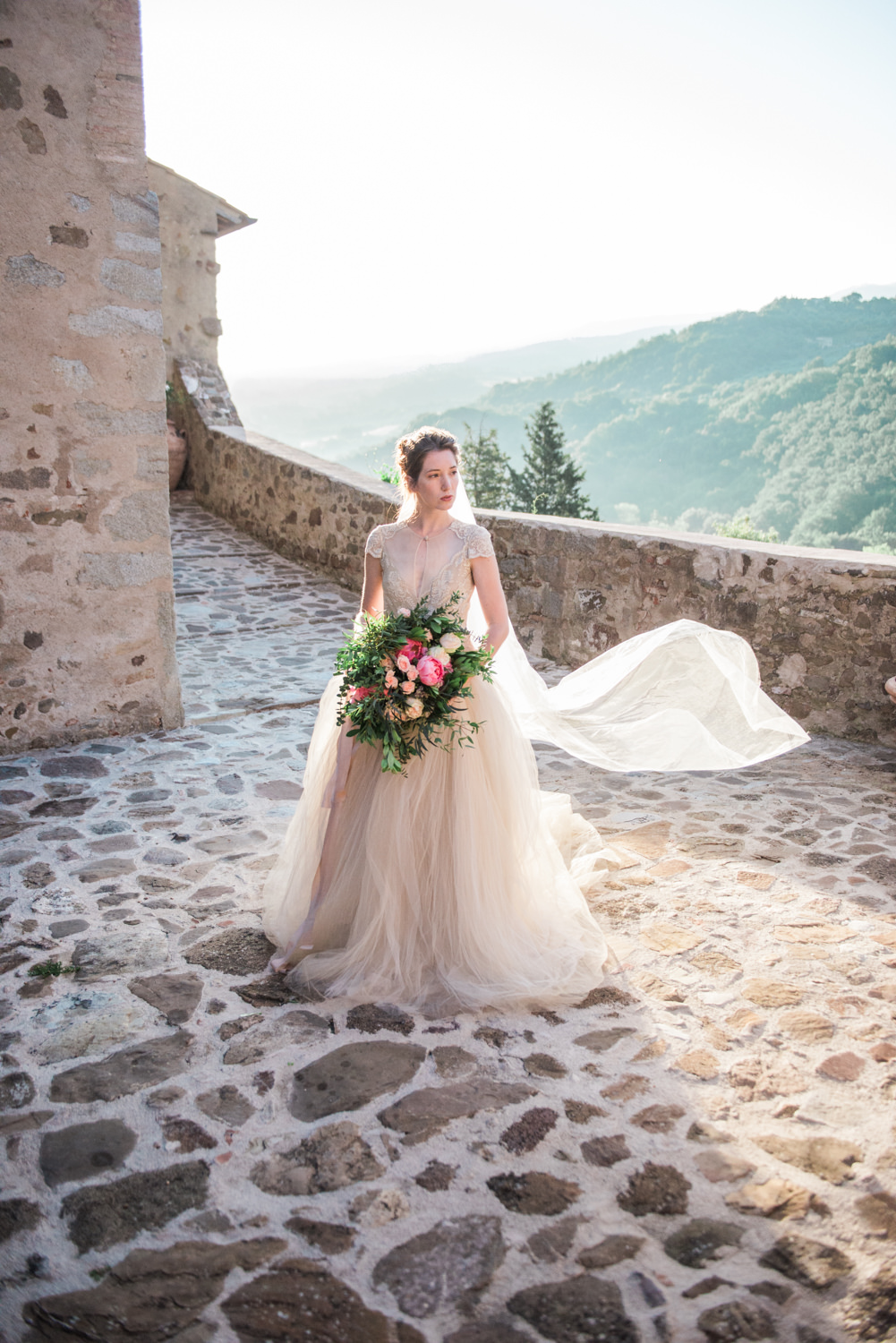 A wedding photographer photographs a wedding in the Tuscan hills of Italy