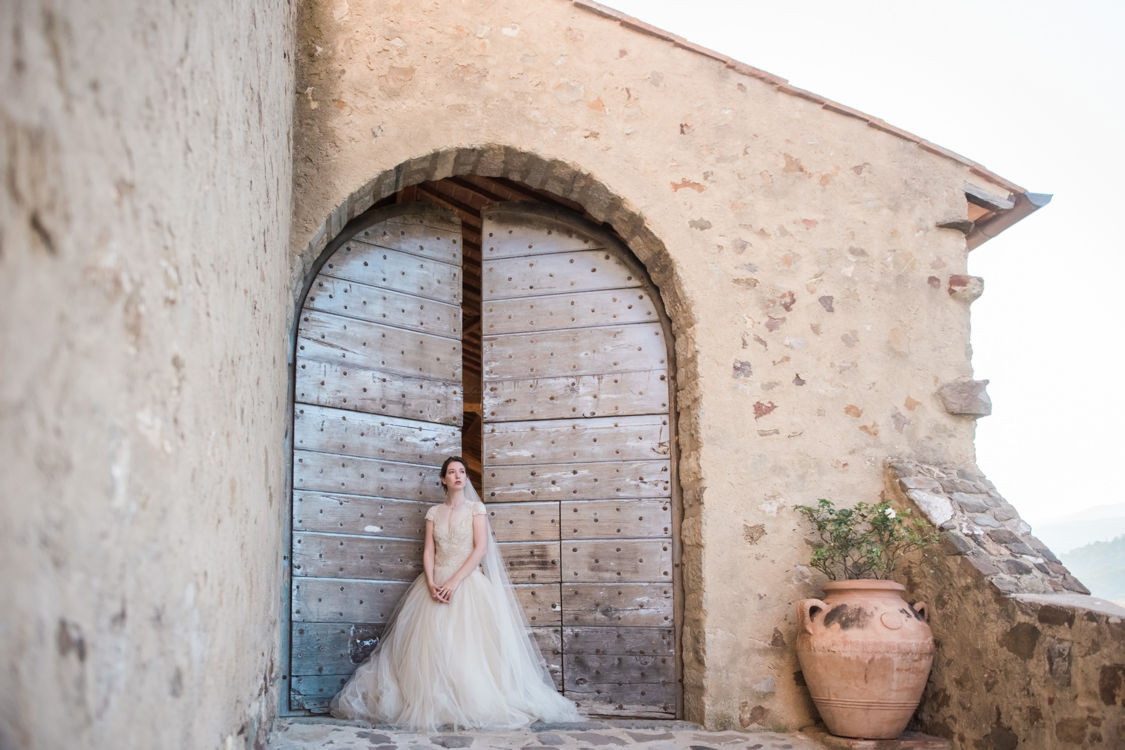 A bride in front of one of the gates ate Castello di Potentino