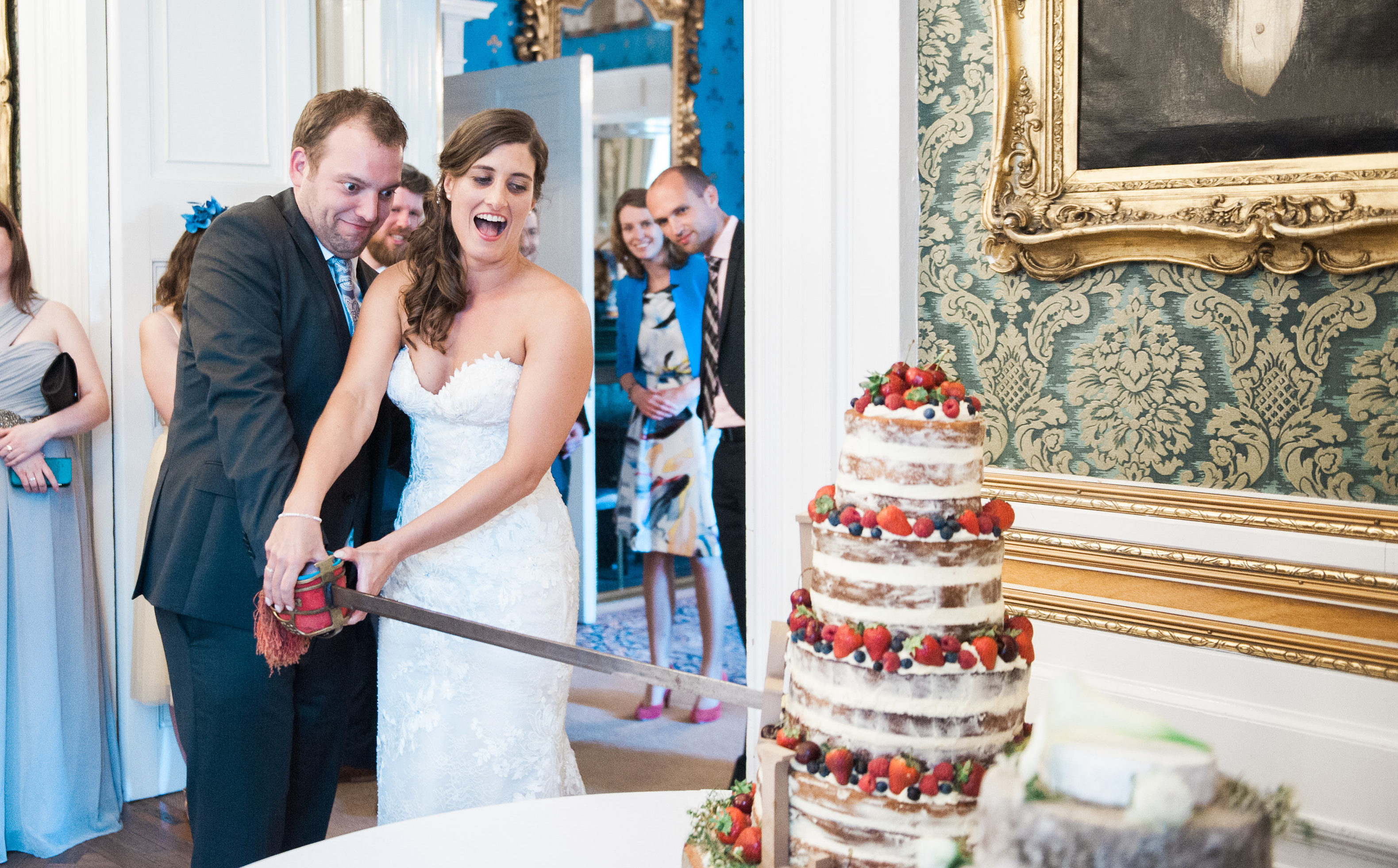 A bride and groom cutting the cake with a sword during their destination wedding in Scotland
