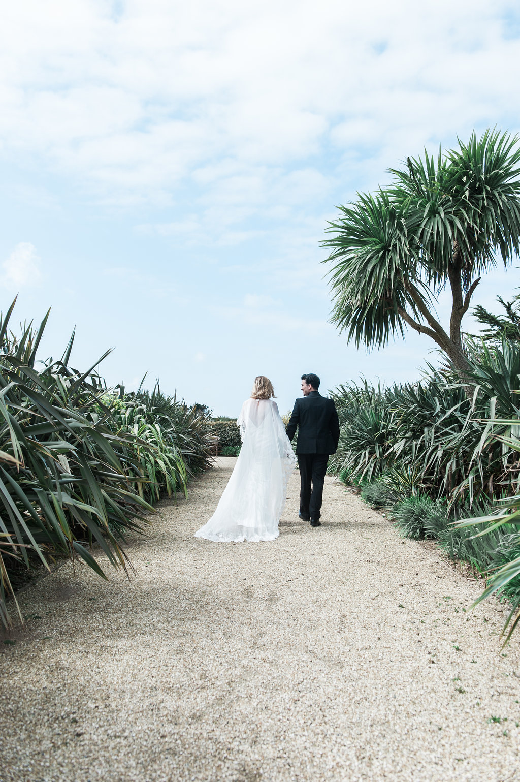 Bride and groom walk on a path surrounded by tropical plants and trees