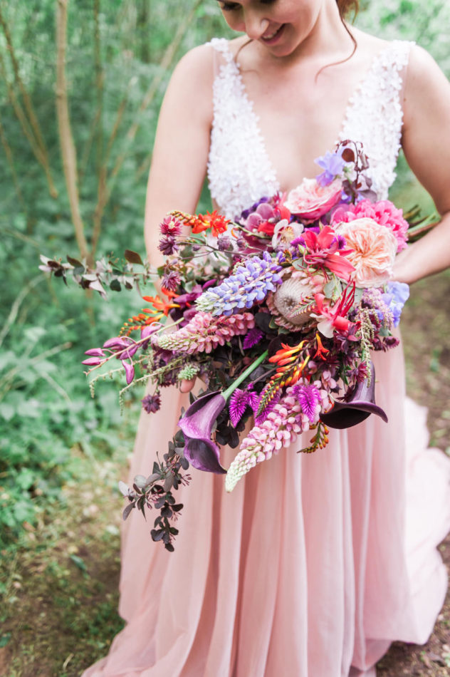 Bride holding a wedding bouquet by Edenique Floral Design while in France, being photographed by a wedding photographer in France