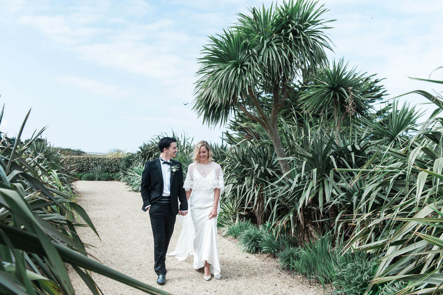 A bride and groom walking on a path in between tropical plants during their destination wedding in Cornwall in The United Kingdom