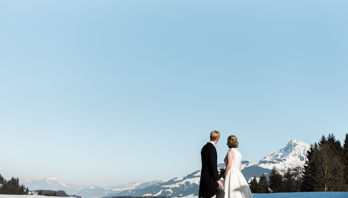 Bride and groom looking at the view over the Austrian Alps, captured by destination wedding videographer Wit Photography