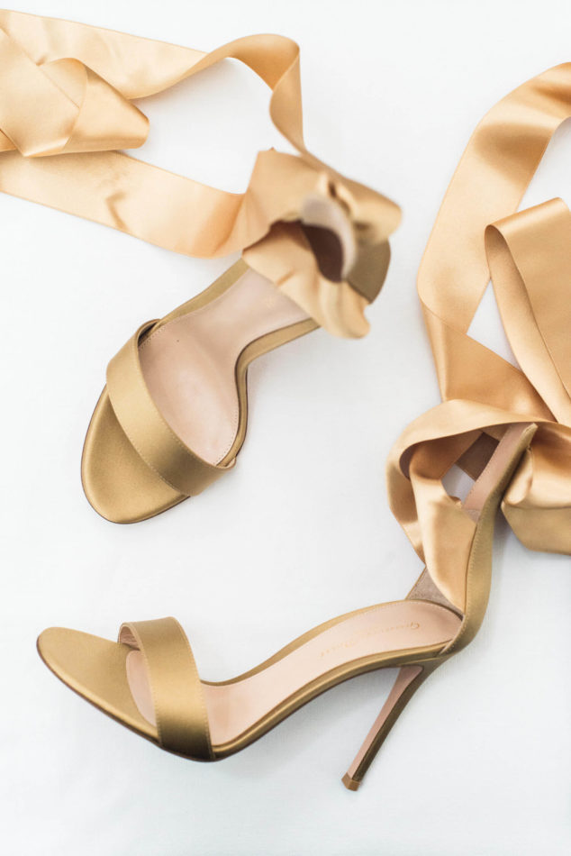 A pair of golden wedding shoes with ribbons