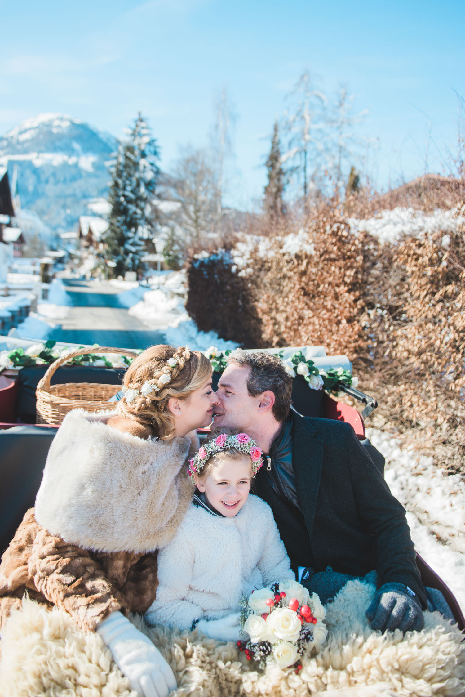 A bride, groom and their daughter in a sleigh during a photo shoot on their wedding day in Austria