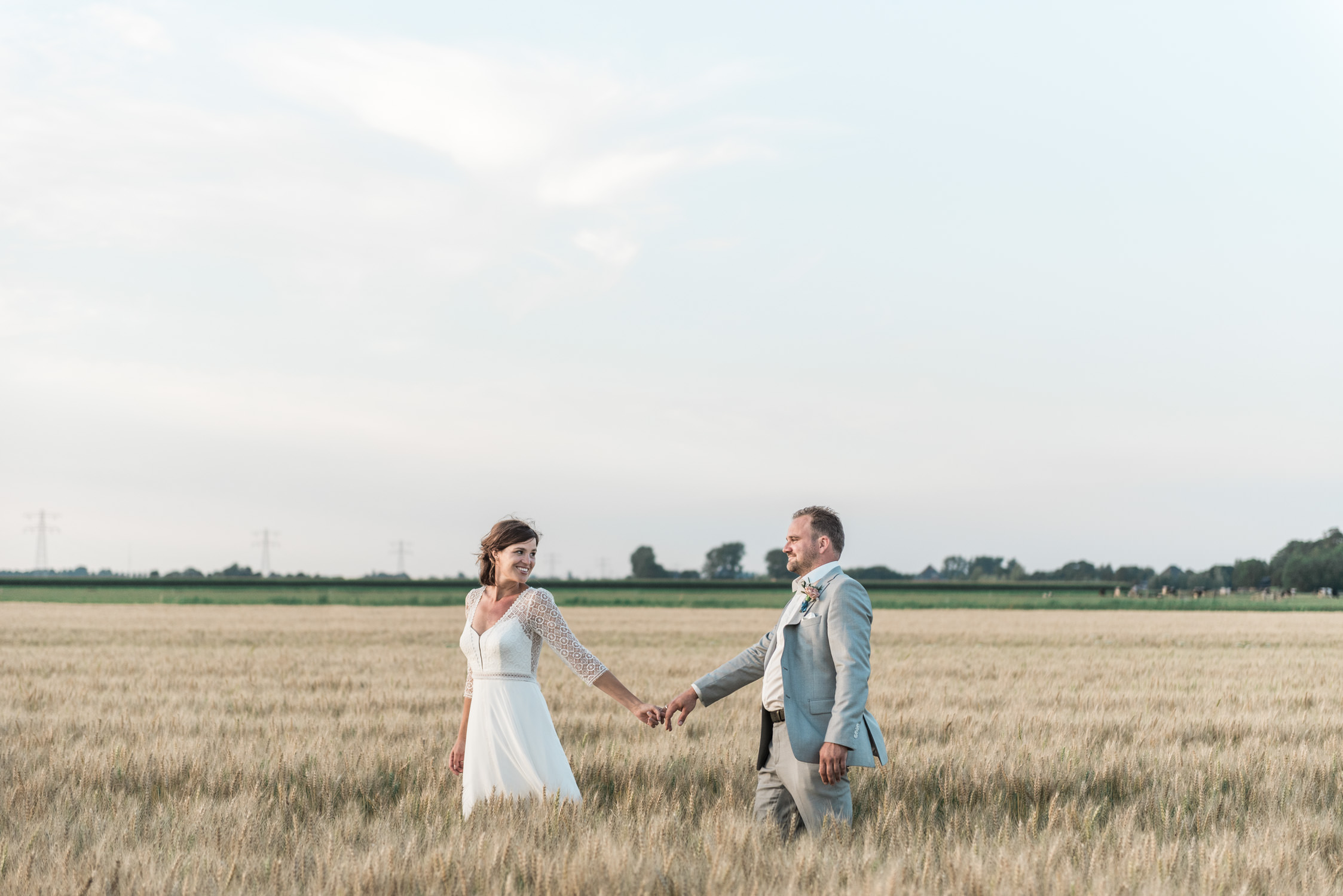 A bride and groom in a wheat field in the netherlands. Captured by Wit wedding photography close to Amsterdam