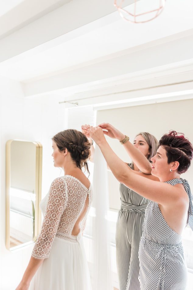 Bride getting her veil placed by two bridesmaids
