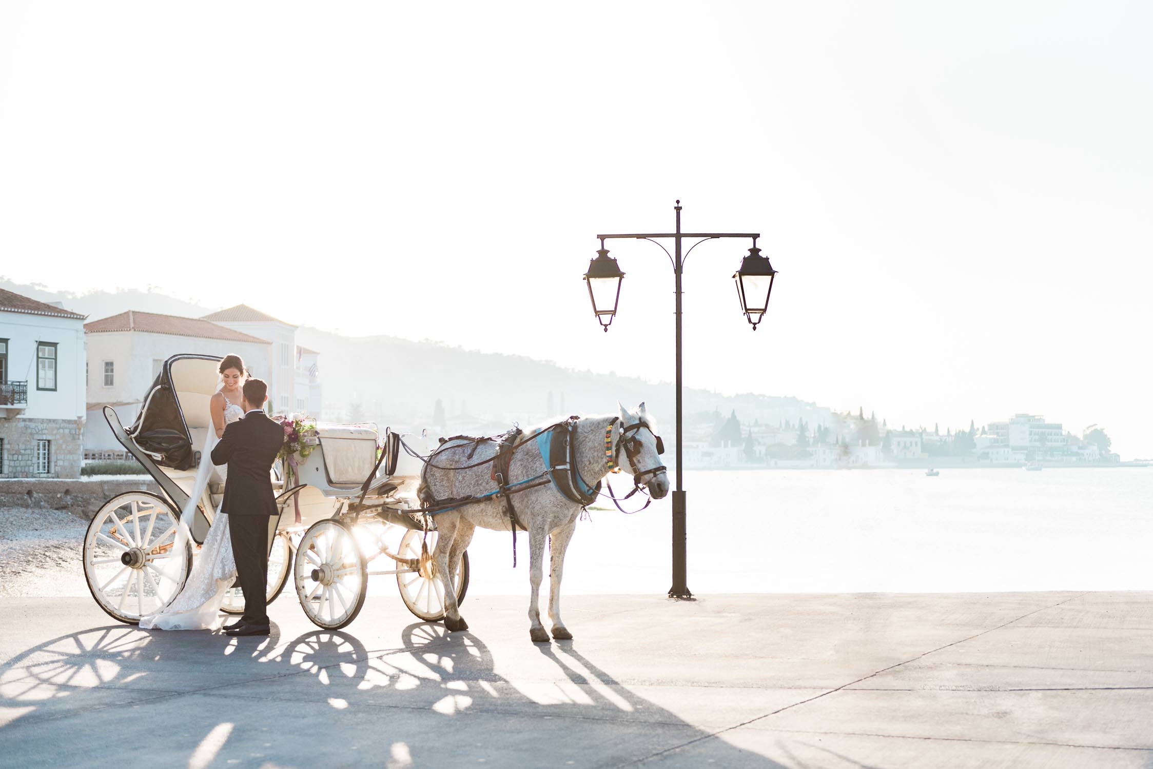 Bride, groom, horse and carriage in front of the Poseidonion Hotel in Spetses during sunset photographed by destination wedding photographer Wit Photography in Greece