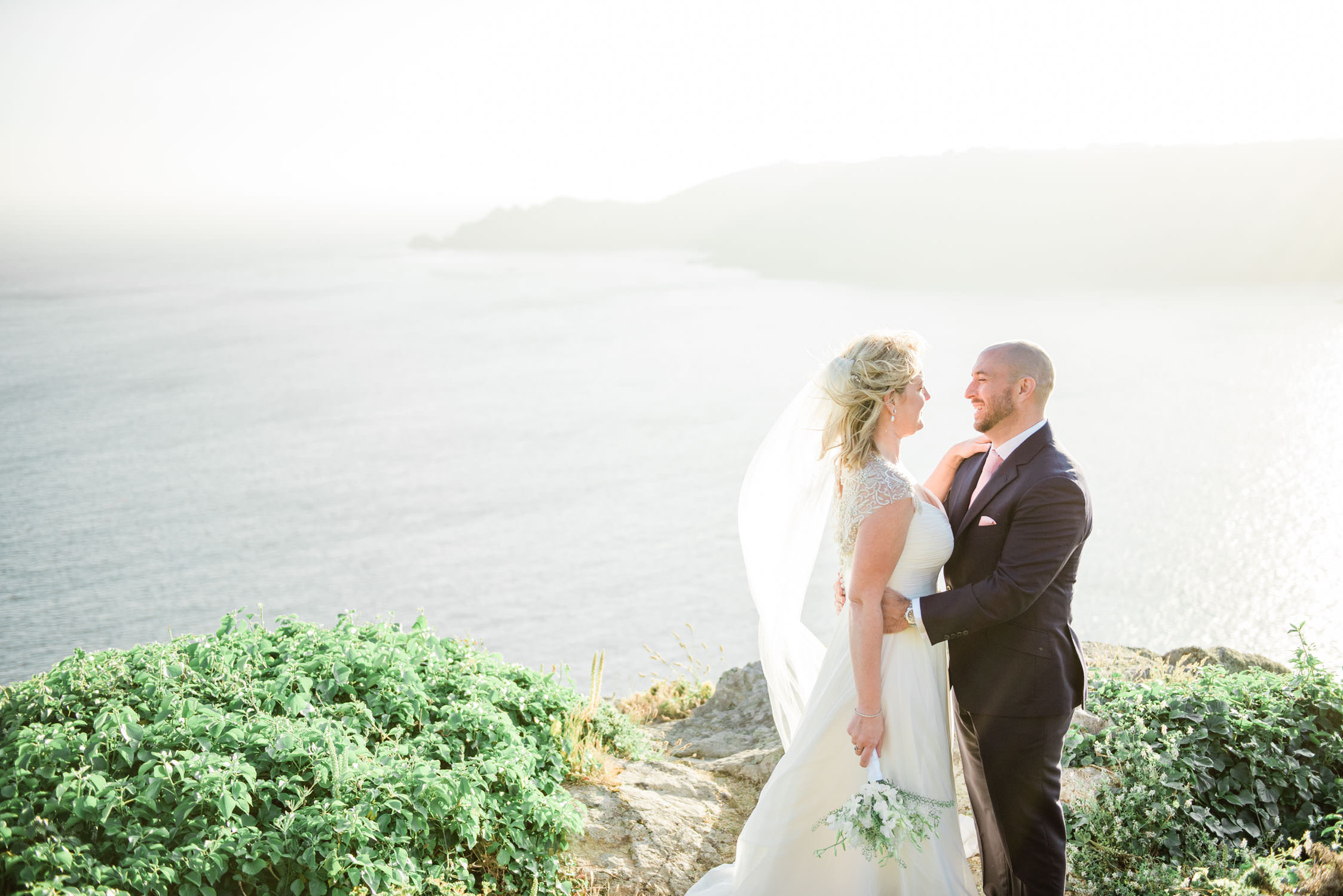 A bride and groom at a cliff in Icard, Guernsey