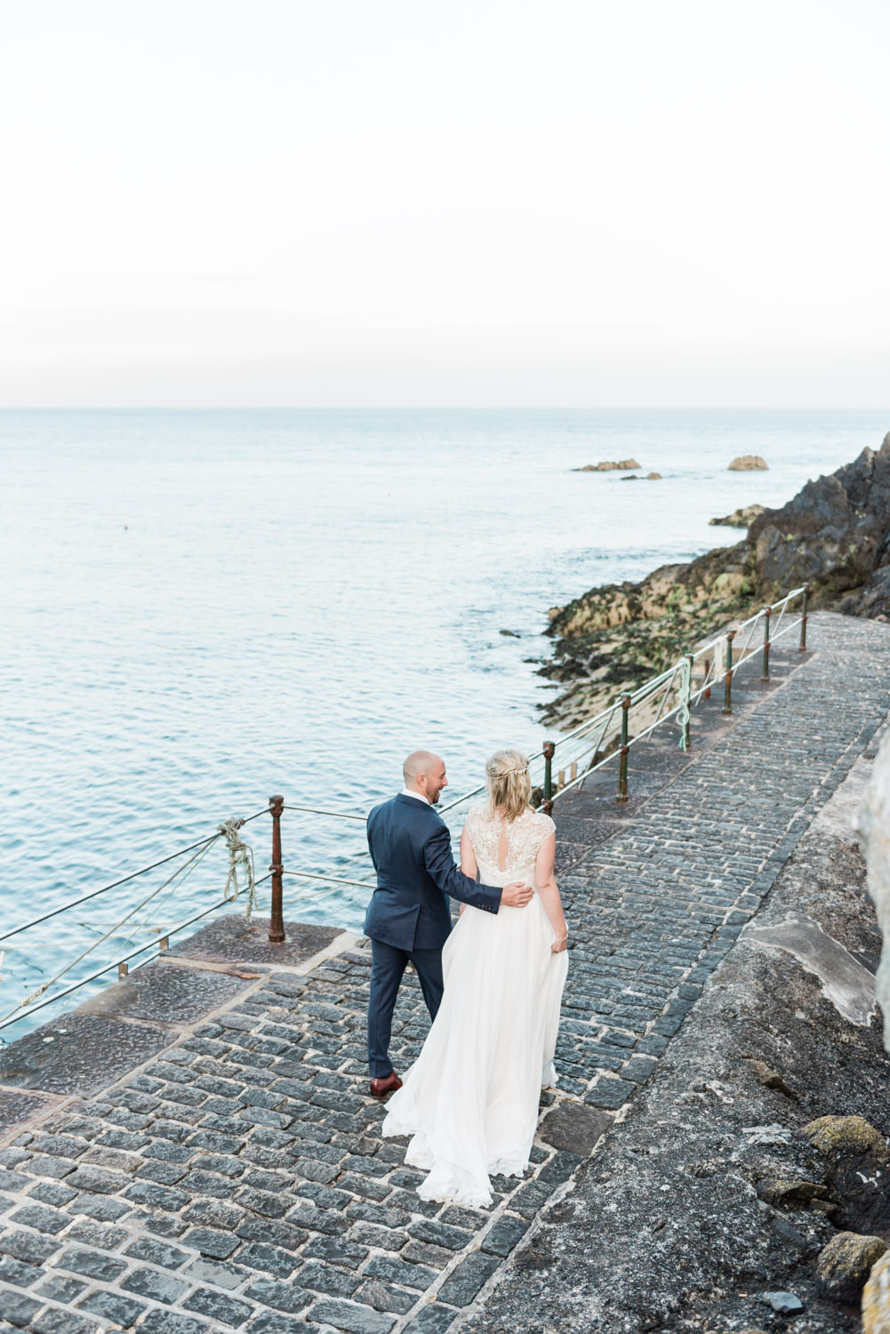 A bride and groom walking near Saint Bay Guernsey at their destination wedding, photographed by destination wedding photographer Wit Photography