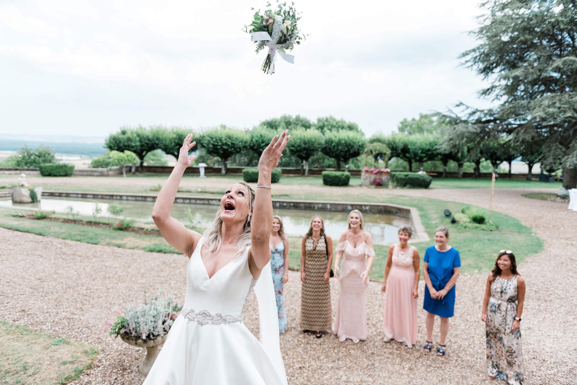 A bride throwing the bouquet at her destination wedding in France