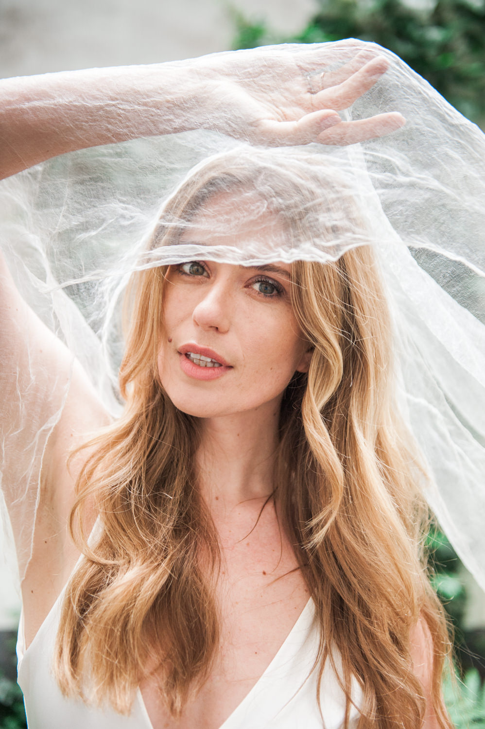A model posing as a bride while holding up a veil