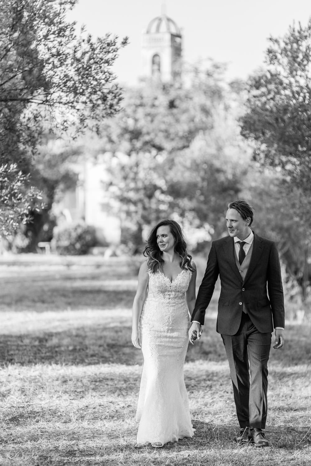 Bride and groom walking in the olive grove of Castell Emporda