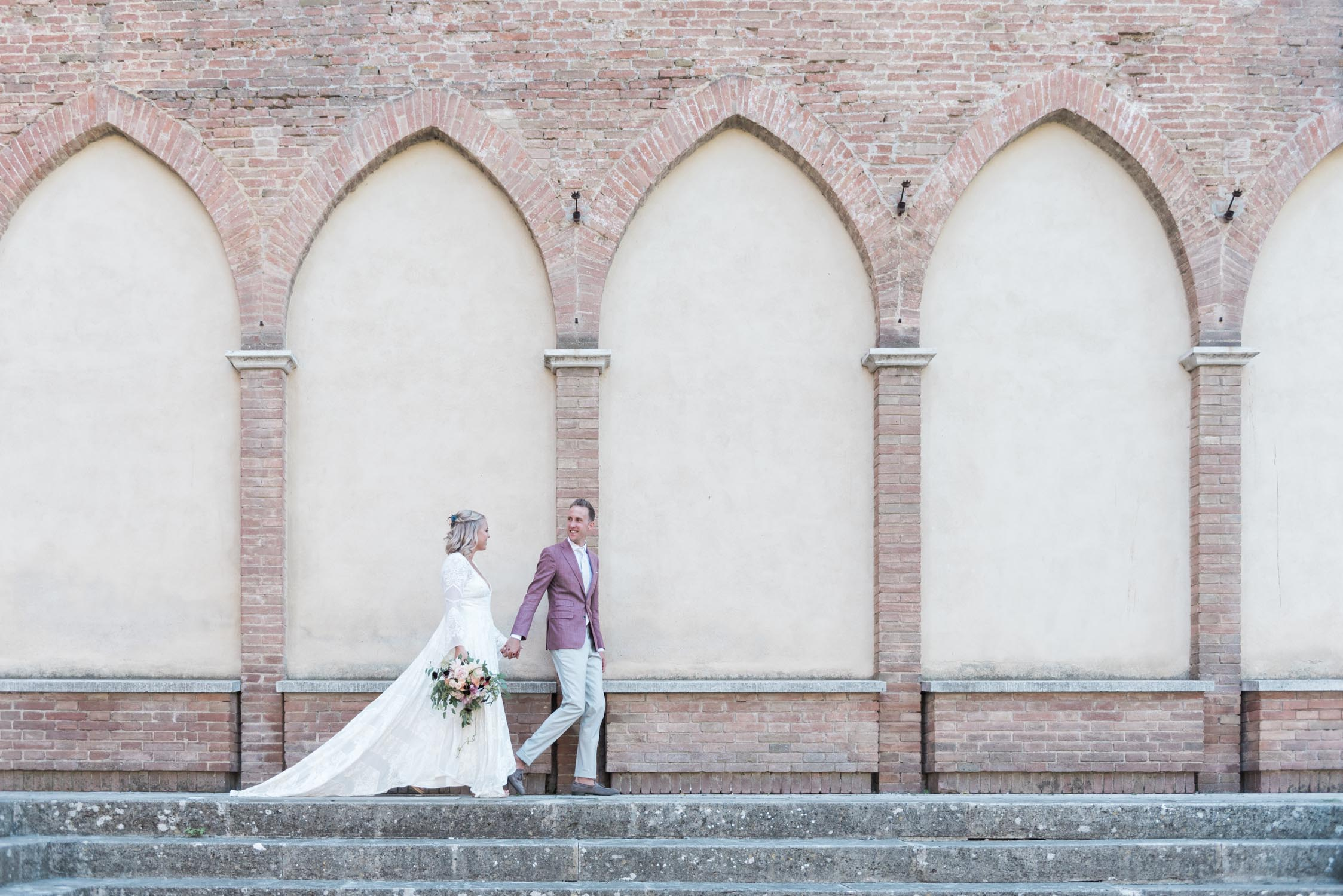 Bride and groom walking past a church in Siena, Tuscany, Italy