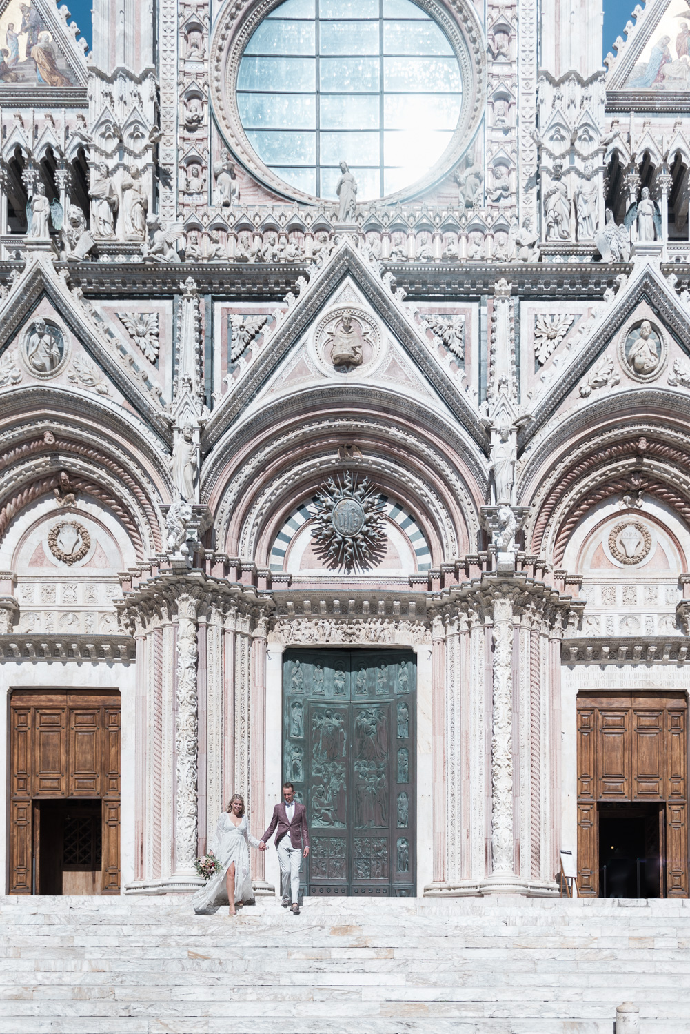 A bride and groom on the steps of the Duomo in Siena, Italy