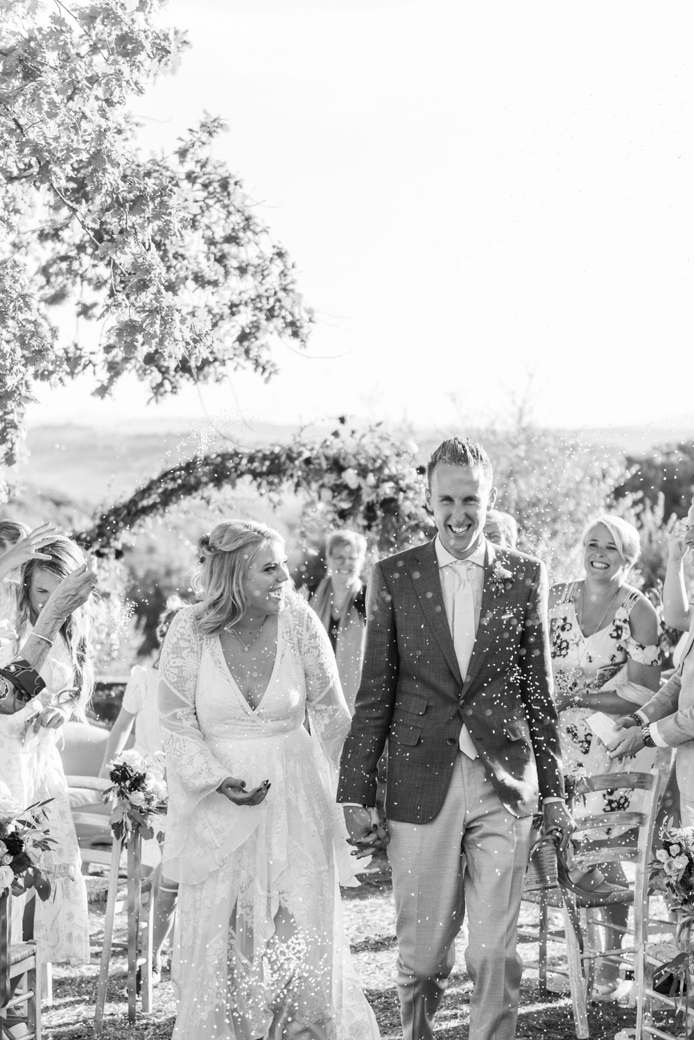 Confettishot of a bride and groom walking out of their ceremony at Fattoria di Corsignano