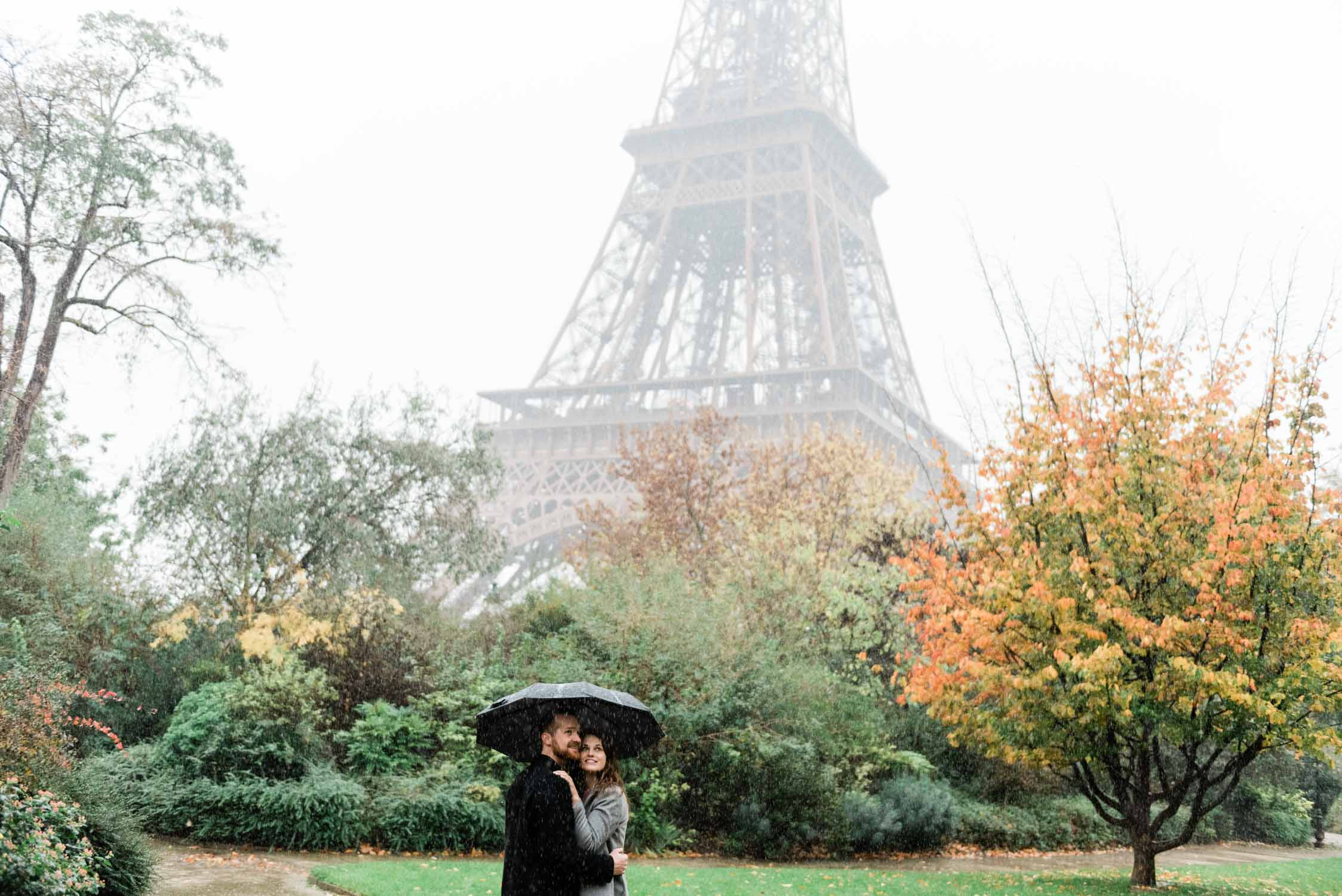 Newly engaged couple in front of the Eiffel tower and fall foliage