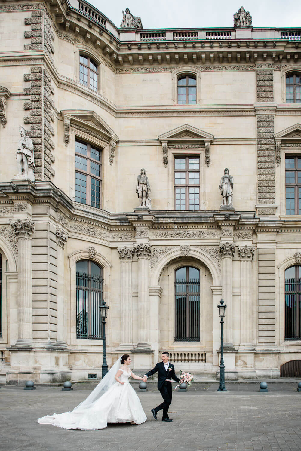 Elopement in Paris photography - a bride and groom run in the streets of Paris